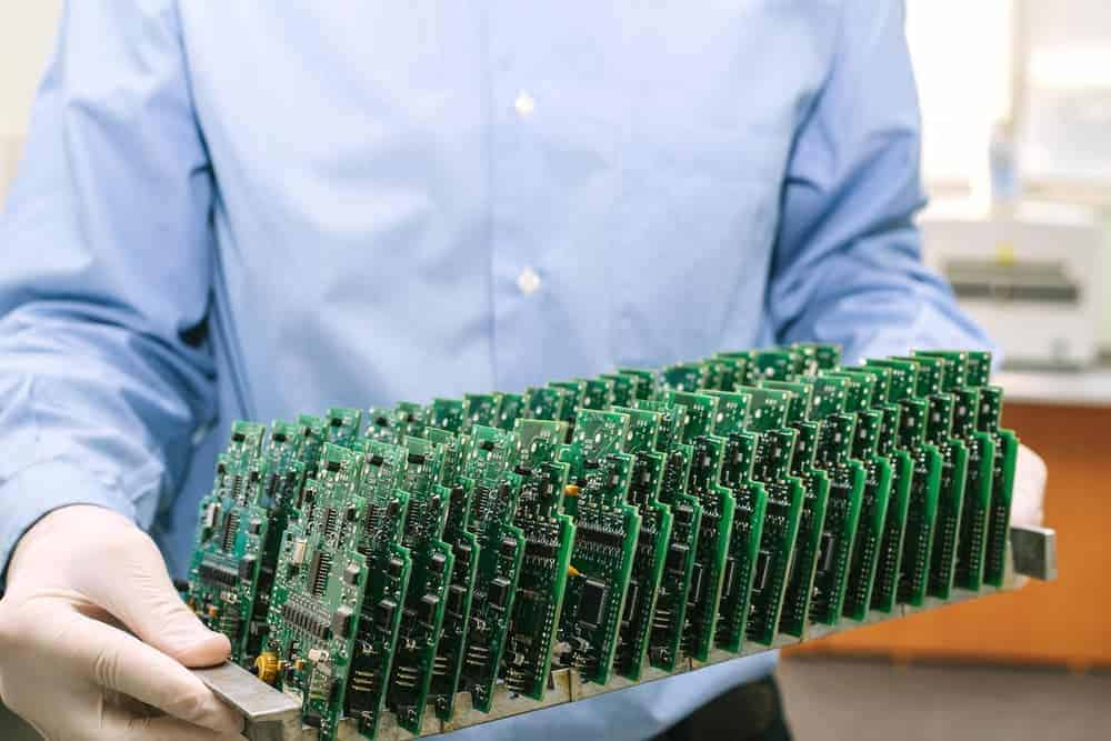 Man holding a tray of circuit boards