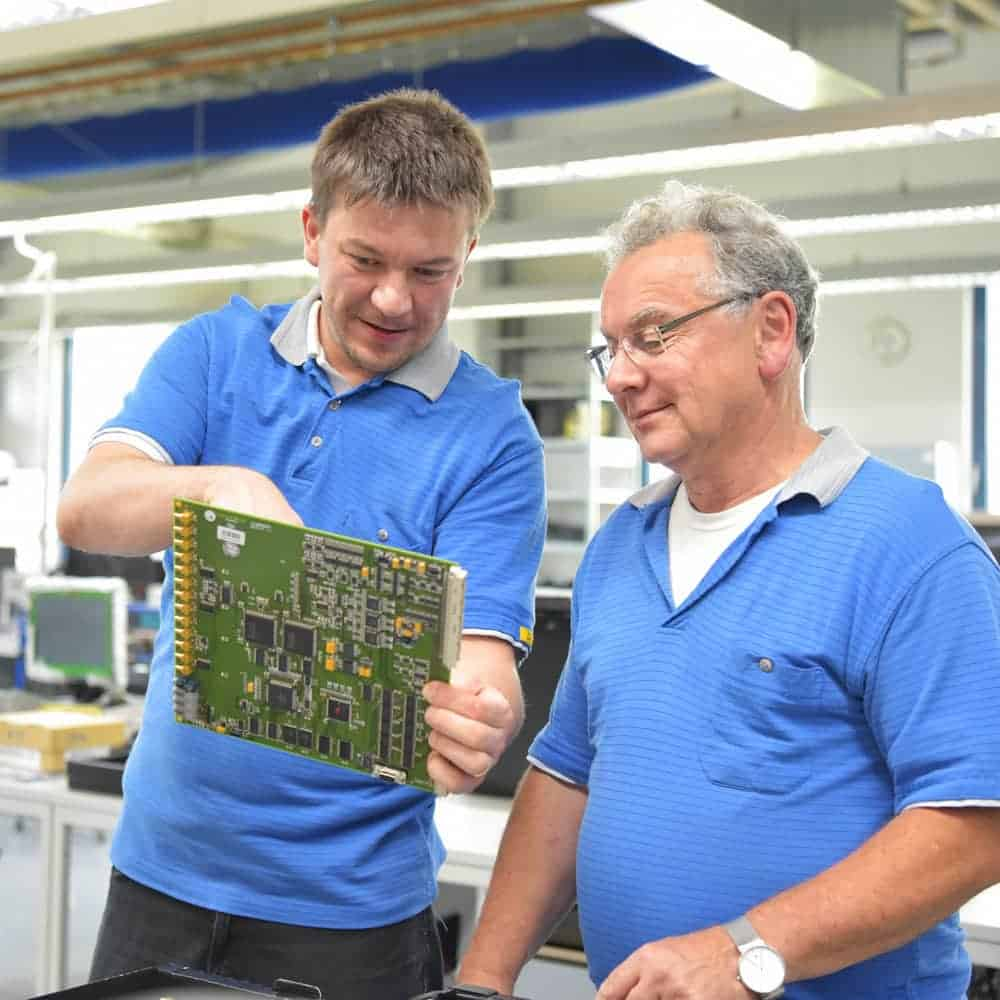 Two workers inspecting a circuit board